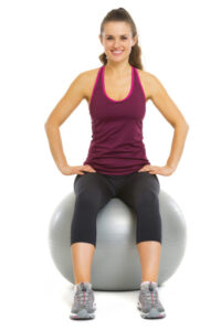 Smiling fitness young woman sitting on fitness ball