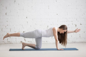 Attractive young woman working out indoors. Beautiful model doing exercises on blue mat in room with white walls. Bird-dog or kneeling opposite arm and leg extension (chakravakasana). Full length